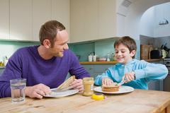 Father and son having peanut butter sandwiches Stock Photos