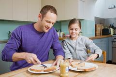 Father and daughter spreading peanut butter on bread Stock Photos