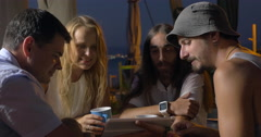 Friends in street cafe watching something funny on pad - stock footage