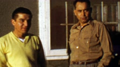 1957: Native Alaskan son with proud father makes funny face. Stock Footage