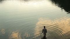 Young countryman standing in the beautiful lake. Reflection of cloudy sunset sky Stock Footage