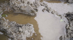 A man in rubber boots walking on the mud Stock Footage