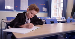 4K Teacher checking on the work of young boy on his own in school classroom Stock Footage