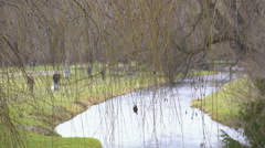 People walking near river in beautiful park, early spring, awakening of nature Stock Footage