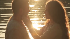 Silhouettes of two lovers kissing by the lake in the evening background Stock Footage