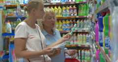 Women choosing household detergents in the supermarket Stock Footage