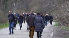 Many people riding bicycles and walking in city park, enjoying fresh spring air - stock footage