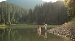 Gorgeous mermaid from the lake in the woods calling man to go with her into the Stock Footage