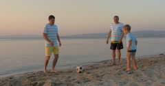 Men of three generations playing football on beach Stock Footage
