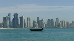Traditional Dhow, Arab sailing vessel in front of the Doha skyline Stock Footage