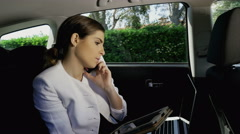 Beautiful elegant business woman working in limousine with tablet and phone 4K - stock footage