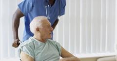 4K Caring medical worker pushing elderly man through hospital in wheelchair Stock Footage