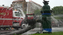 Fire hydrant sparys water, fire trucks in background. Stock Footage
