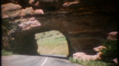 3307 automobile drives through tunnel carved out rock - vintage film home movie Stock Footage