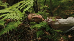Beautiful young mythological dryad from carpathain forest lying on the fern and Stock Footage