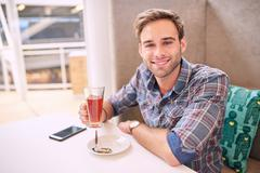 Good looking man looks straight at camera sitting in cafe - stock photo