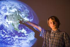 Boy with projection of earth - stock photo