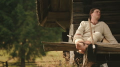 Young carpathian countryman in traditional ukrainain clothes sitting on the Stock Footage