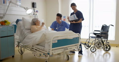 4K Caring medical workers in hospital talking to elderly lady at her bedside Stock Footage