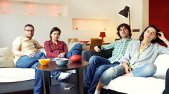 Unhappy friends watching television and talking with each other Stock Footage