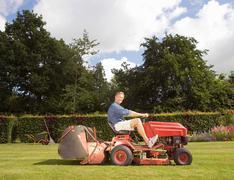 Man mowing a lawn Stock Photos