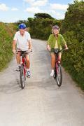 Senior couple cycling on country lane - stock photo