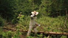 Young countryman woodcutter in traditional ukrainain clothes in the green forest Stock Footage