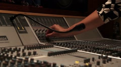 Recording studio music mixing desk console with engineer hand turning nob Stock Footage