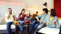 Friends sitting on the sofa and talking on loudspeaker - stock footage