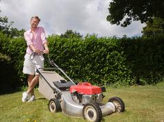 Man with push lawnmower Stock Photos