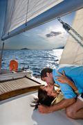 Couple laying on sailboat, kissing Stock Photos