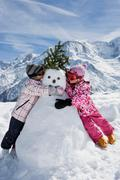 Two girls with a snowman Stock Photos