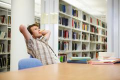 Young man working in library - stock photo