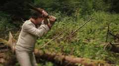 Young countryman woodcutter in traditional ukrainain clothes chopping wood in - stock footage