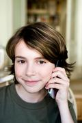 Boy is phoning with his mobile phone - stock photo