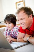 Father and son smiling into laptop Stock Photos