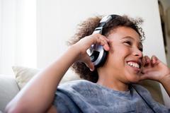 Boy with big earphones enjoying music Stock Photos