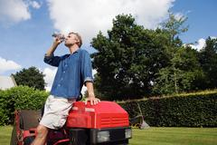 Man drinking water by lawn mover Stock Photos