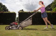 Women with push lawnmower Stock Photos