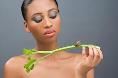 Woman looking at a snail on a stick of celery Stock Photos