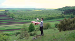 Cute child plays with toy airplane on the green mountain. 4k Stock Footage