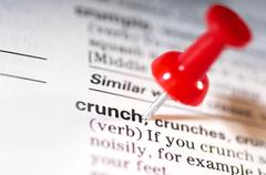 Thumb tack on word crunch Stock Photos