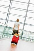 Woman dragging a suitcase Stock Photos