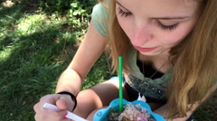 Young teenage girl eating shaved ice snow cone at summer time 4k Stock Footage