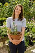 A portrait of female holding a plant pot Stock Photos