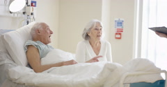 4K Cheerful senior couple in hospital room & medical worker talking to them Stock Footage