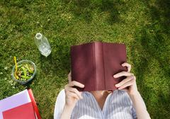 Business woman reading book in park - stock photo