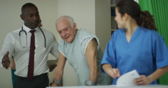 4K Caring medical workers in hospital assisting elderly man on crutches Stock Footage