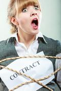 Afraid businesswoman bound by contract terms. - stock photo