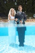 Bride and groom in pool with bubbles Kuvituskuvat